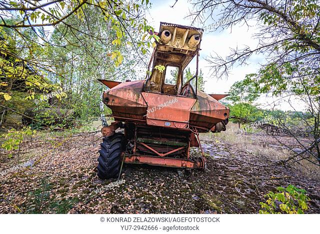 Old combine harvester in station for agricultural machines of abandoned kolkhoz near Zymovyshche village in Chernobyl Zone of Alienation, Ukraine