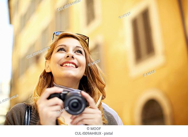 Young woman with digital camera, Rome, Italy