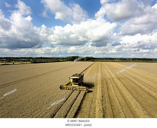 A drone shot of fields in a farming landscape, and a combine harvester working harvesting a crop