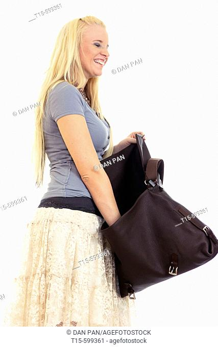 Young girl in her 20's reaching into her hand bag to find stuff/to have some fun/to look for missing stuff