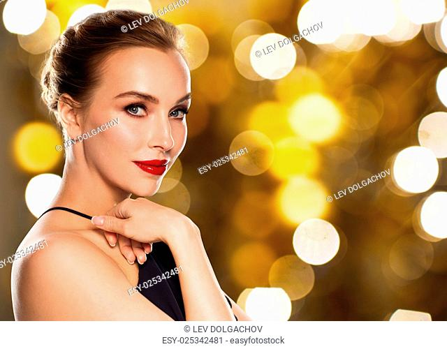people, luxury and holidays concept - beautiful woman in black with red lips over lights background
