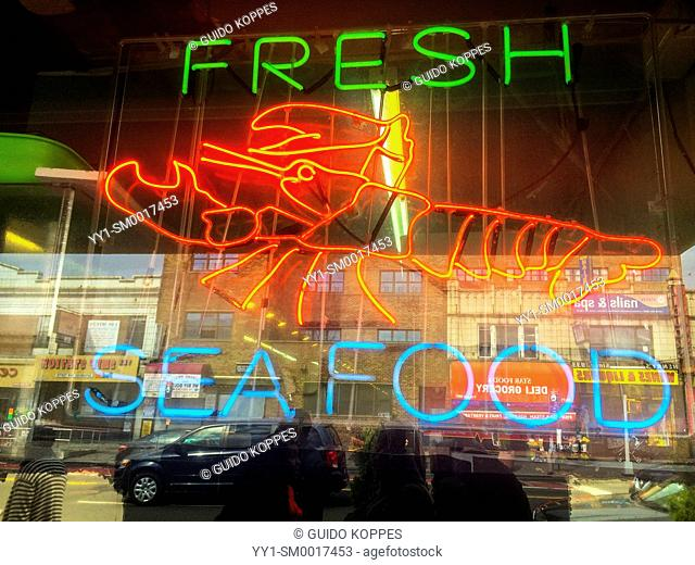 New York City, USA. Neon sign inside the window to a fresh seafood and fish store, Roosevelt Av, Queens