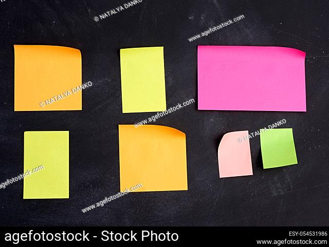 empty paper multi-colored stickers are glued on a black board, place for an inscription