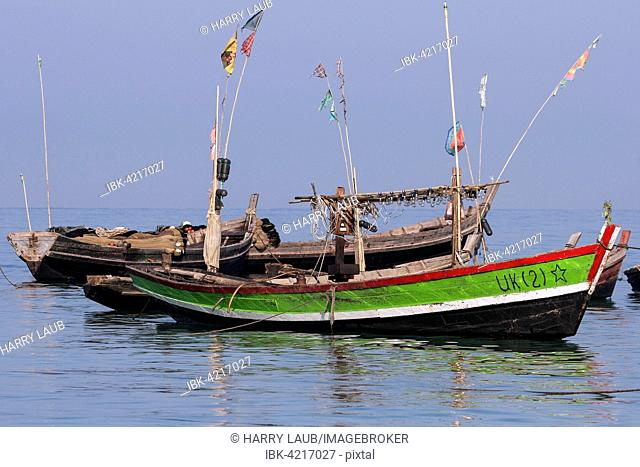 Colourful fishing boats in the sea off the beach of the fishing village of Ngapali, Thandwe, Rakhine State, Myanmar