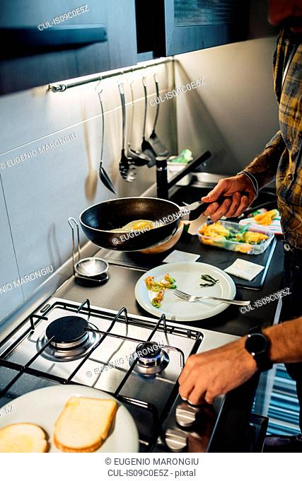 Mid adult man preparing fried eggs at kitchen hob, cropped