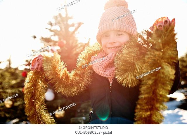 Girl in christmas tree forest wearing tinsel, portrait