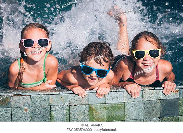 Three happy children playing on the swimming pool at the day time. Kid having fun outdoors. Concept of friendly family
