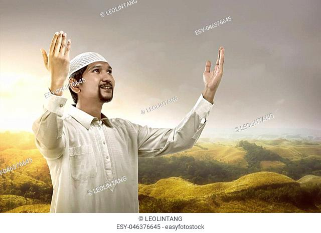 Image of young muslim man praying on the mountain