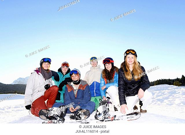 Young friends sitting together in ski resort