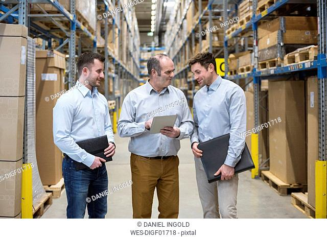 Three men with tablet talking in factory warehouse
