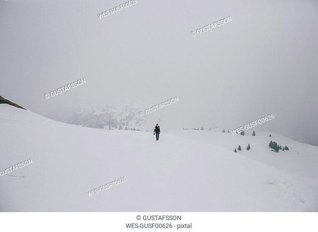 Austria, Kitzbuehel, woman walking in snow-covered landscape
