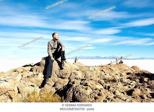 Bolivia, Atacama, Altiplano, Salar de Uyuni, man sitting on stone