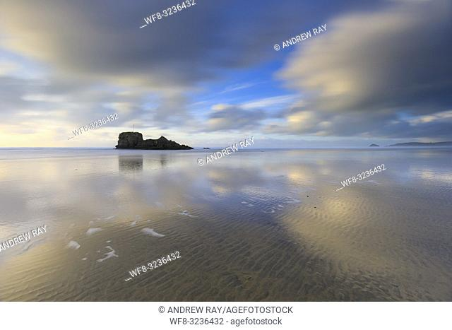 Clouds reflected in the wet sand on Perranporth Beach on the North Coast of Cornwall, with Chapel Rock in the distance. The image was captured using a long...