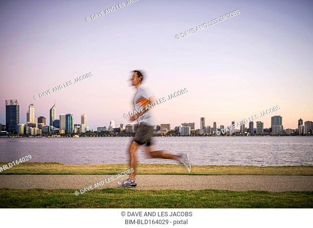 Blurred view of Caucasian man running near urban waterfront, Perth, Western Australia, Australia
