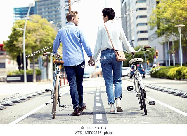 Couple with bikes in Barcelona, rear view
