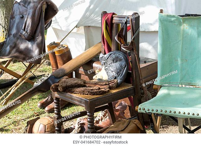 Vintage pilot gear on wooden chair, aircraft propeller, and other antiquities by a tent outdoors