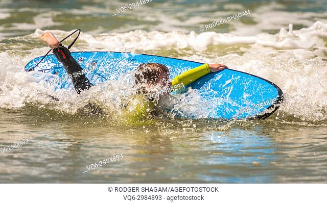 Young boy falls off his surfboard during a surfing lesson. Cape Town, South Africa