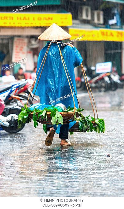 Woman carrying baskets with grocery in heavy rain in the old quarters of Hanoi, Vietnam