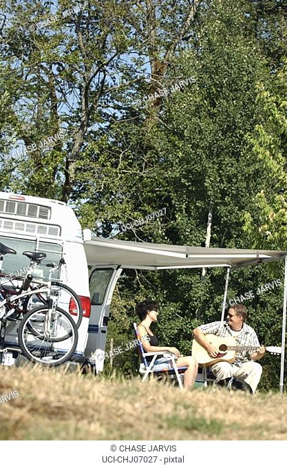 Couple camping and playing guitar