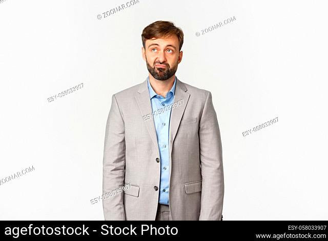 Portrait of skeptical and upset bearded male office worker in grey suit, looking disappointed at upper left corner logo, standing over white background