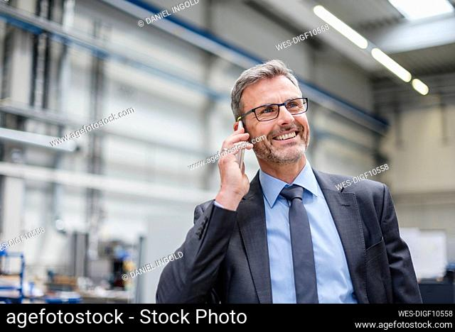 Smiling businessman on the phone in a factory