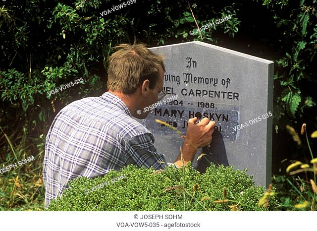 A man carving a gravestone at Kilcatherine Church in Cork, Ireland