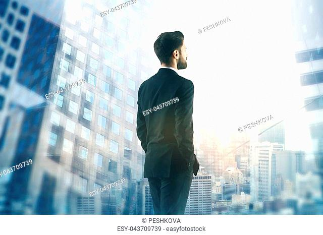 Back view of young businessman looking at blurry city. Research concept. Double exposure