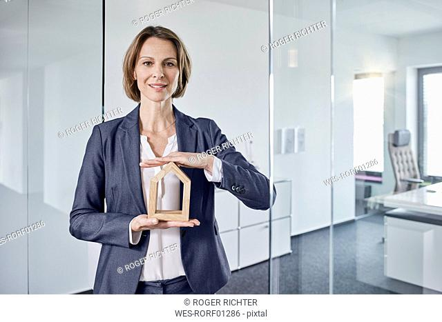 Portrait of businesswoman holding architectural model in office
