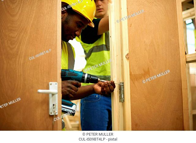 Male higher education students drilling wooden doorway in college workshop