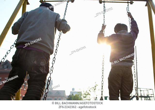 Kathmandu Nepal Nepali boys play on swing set in the morning in Nayapati, Eastern Kathmandu 1