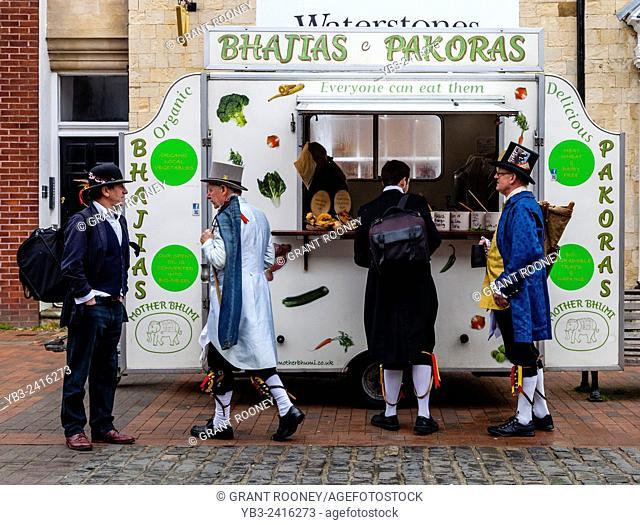 Sompting Village Morris Dancers Buying Snacks From A Mobile Food Shop, High Street, Lewes, Sussex, UK