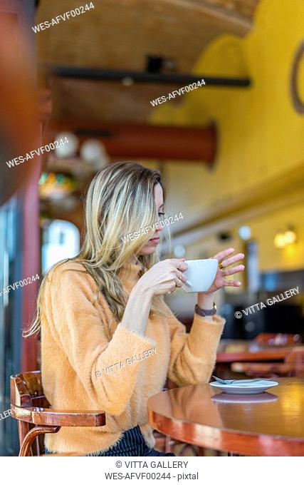 Pensive young woman in a cafe holding cup of coffee