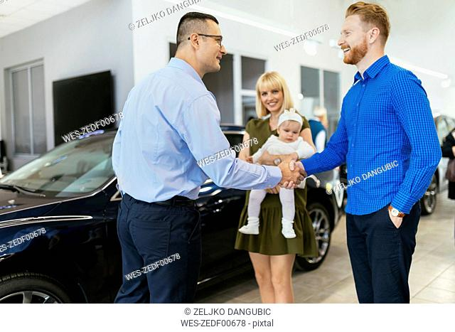 Family meeting seller of family vehicle in car dealership