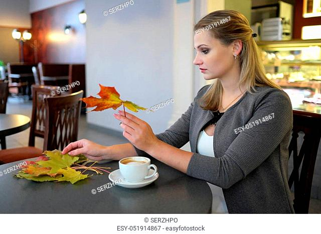 attractive young woman with colour leaves sitting in a cafe with a cup of coffe closeup portrait