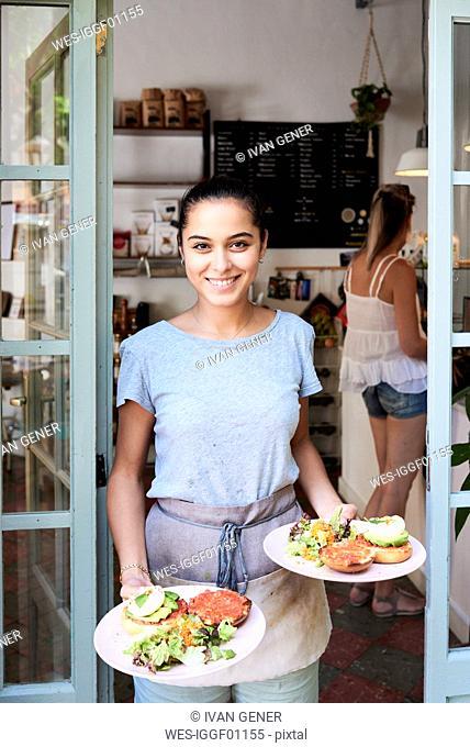 Portrait of smiling waitress serving breakfast