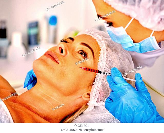 Woman middle-aged in spa salon with doctor. Beauty female giving botox injections