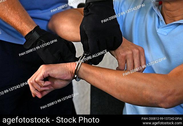 12 August 2020, Saxony, Chemnitz: Judicial officers are removing the handcuffs from a man accused of double murder at Chemnitz Regional Court