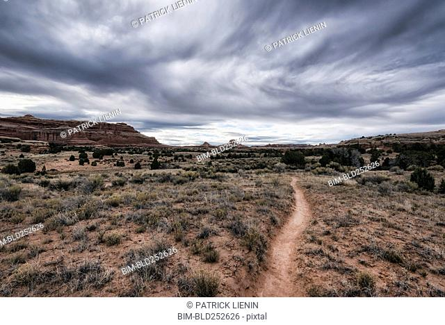 Clouds over desert path, Moab, Utah, United States