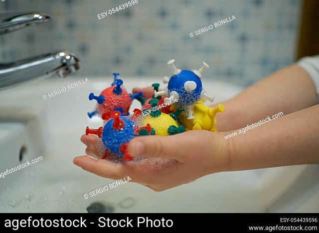 Hands holding models of coronavirus in soapy water