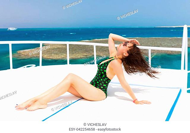 Young woman in black-green swimsuit lying on the deck of the yacht at a sunny summer day, breeze developing hair, beautiful sea on background