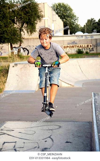 boy is jumping with a scooter over a spine in the skate parc and enjoying it