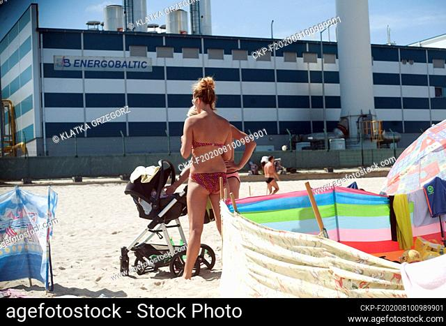 Poland, Wladyslawowo 10.08.2015. Tourists at the beach in popular seaside resort with Energobaltic company buildings in the background