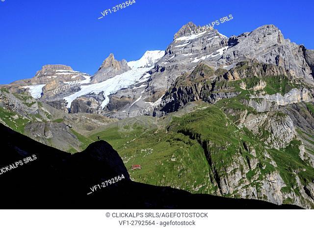Hiker admires Lake Oeschinensee Bernese Oberland Kandersteg Canton of Bern Switzerland Europe
