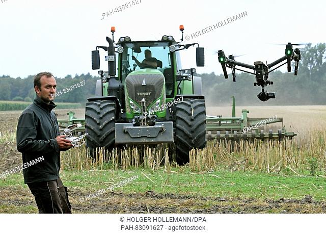 Joern Glaeser films a Fendt 939 Vario tractor with short disc harrow by use of a drone in a field near Rodewald in the region of Nienburg, Germany
