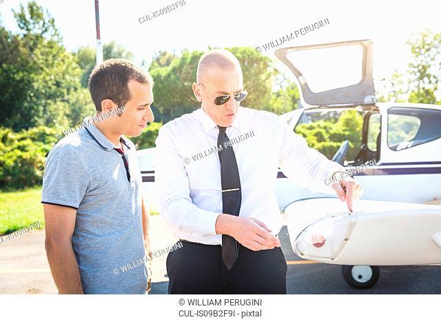 Pilot speaking with aircraft passenger before flight