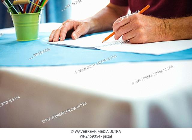 Close-up of hands writing on white paper on a retirement home