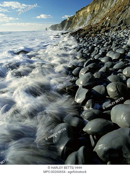 High tide on a boulder strewn beach on the North Taranaki Coast, south of Tongaporutu, New Zealand