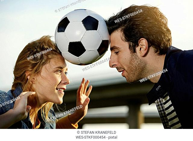 Germany, Dusseldorf, Young couple playing football