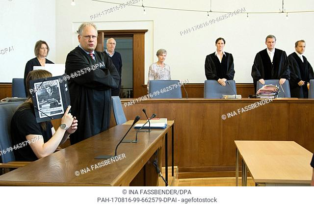 Defendant Iwan K. holds a folder in front of his face at the start of the trial, sitting beside his lawyer Ralf Bleicher (r) at the regional court in Dortmund