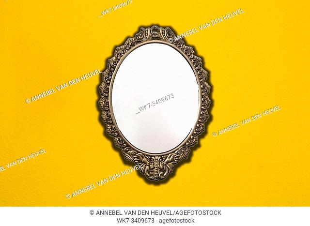 Vintage mirror on retro yellow wall background texture, space for text